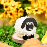 Pom pom sheep in front of yellow flowers