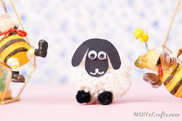 Pom pom sheep on pink surface with floral background