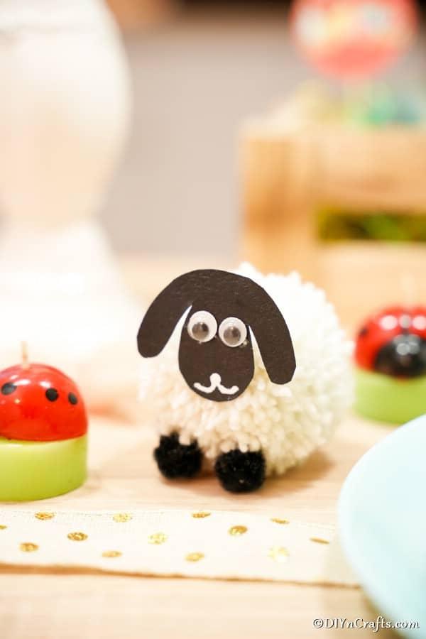 Pom pom sheep on table with mini ladybug