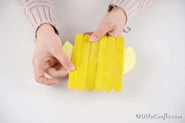 Gluing wings onto craft stick chicken