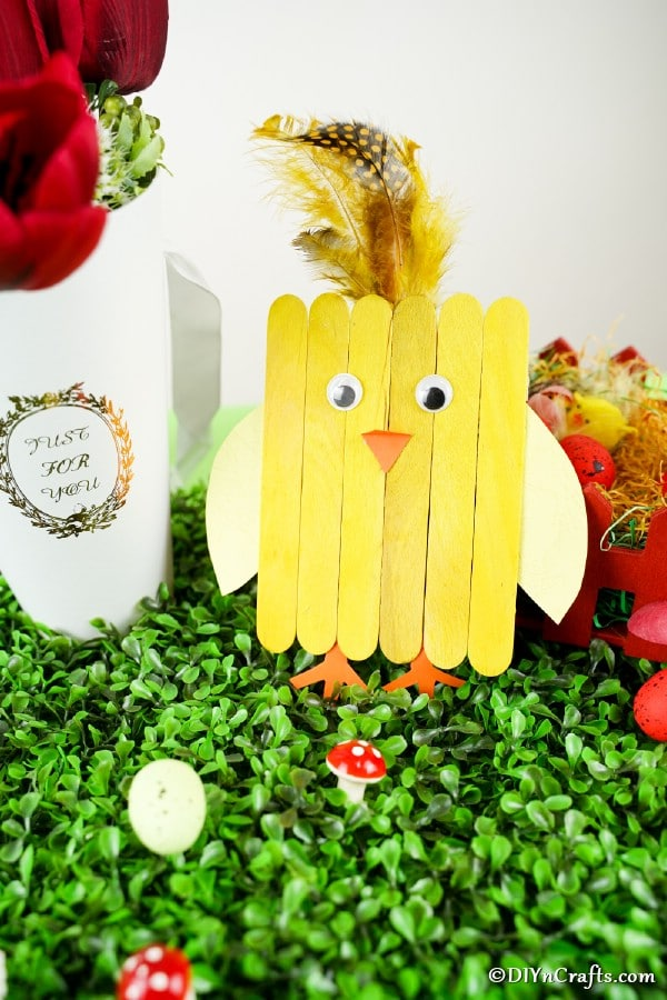 Yellow craft stick chicken next to Easter decor