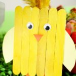 Yellow popsicle stick chick leaning against grass