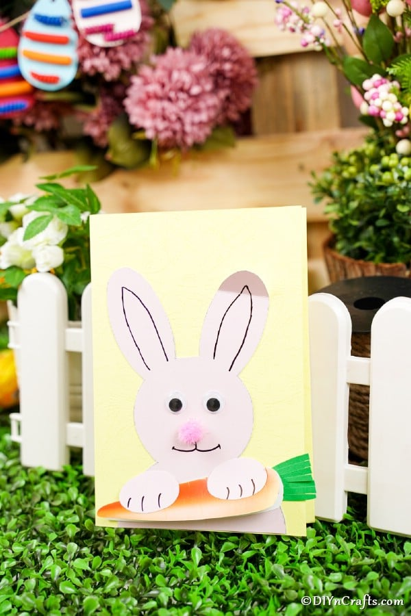 Easter bunny card propped against tiny white fence