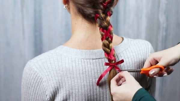 Tying ribbon in a bow on hair