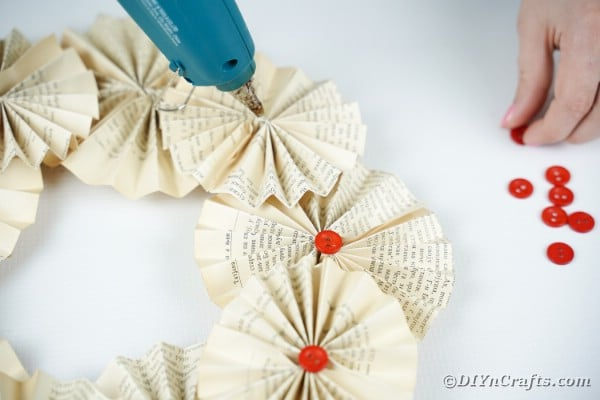 Gluing buttons onto wreath as accents