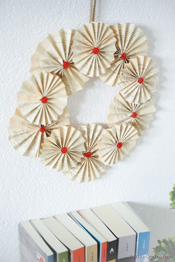 Book page wreath on wall above books