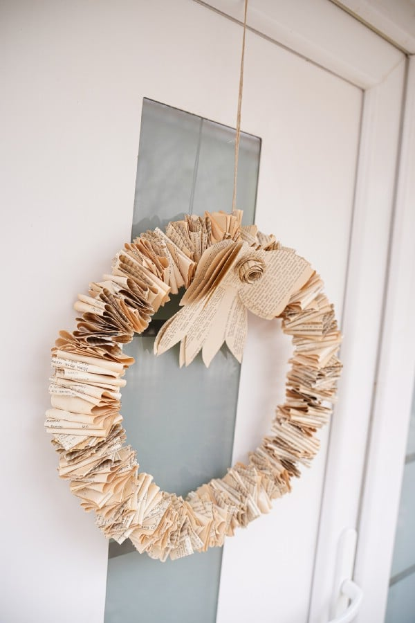 Folded book page wreath hanging on door