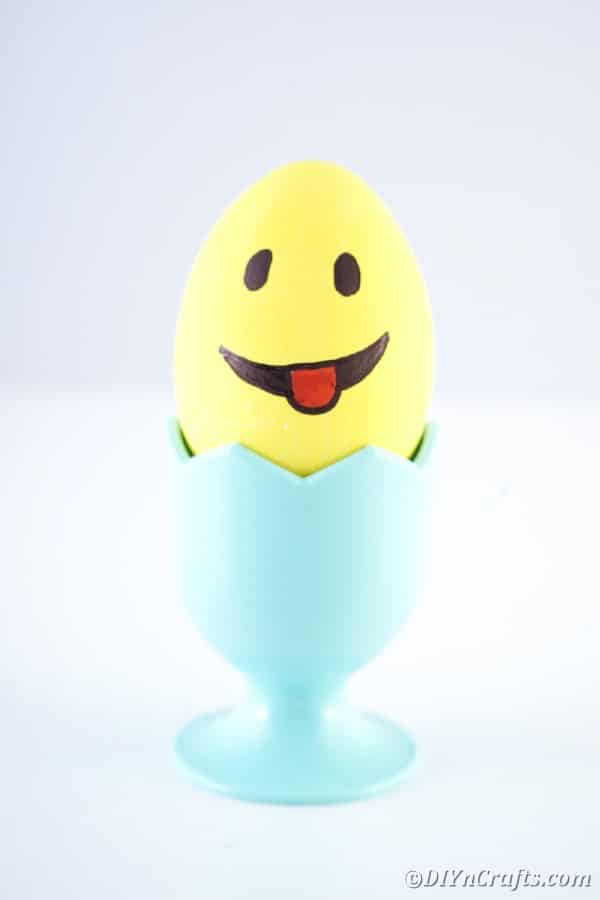Yellow Easter egg in blue egg cup