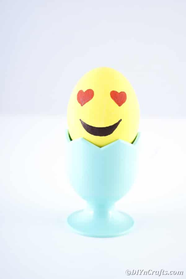 A heart eyed emoji egg in egg cup