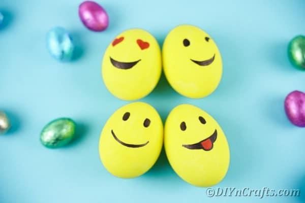 Emoji eggs on blue surface