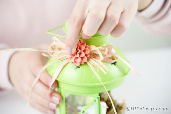 Adding flower to raffia bow