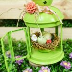 Green lantern easter craft on grass by wooden box