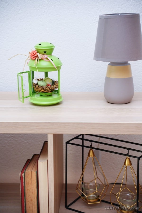 Spring nest lantern on table by lamp