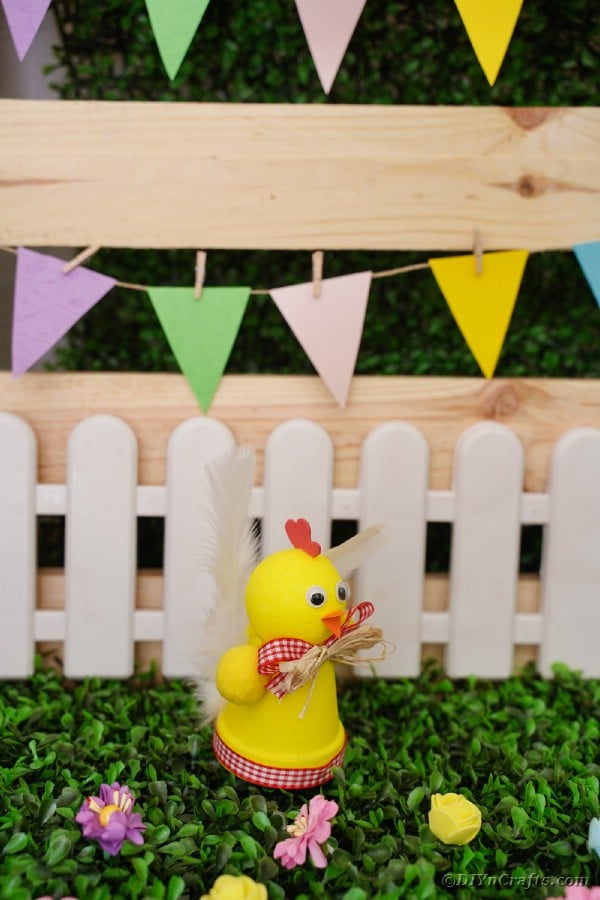 Chicken planter craft in front of white fence