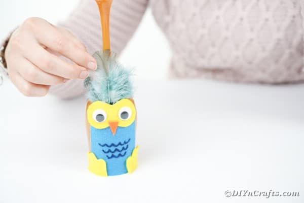 Gluing feathers to wine glass owl