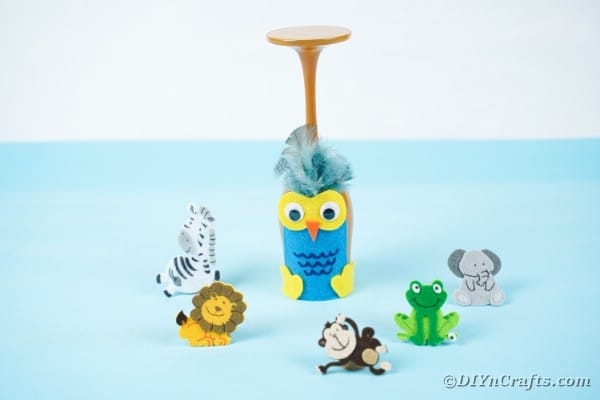 Wine glass owl on blue table surrounded by toy animals