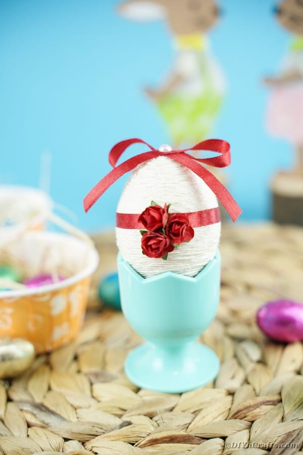 Yarn egg in cup on woven mat