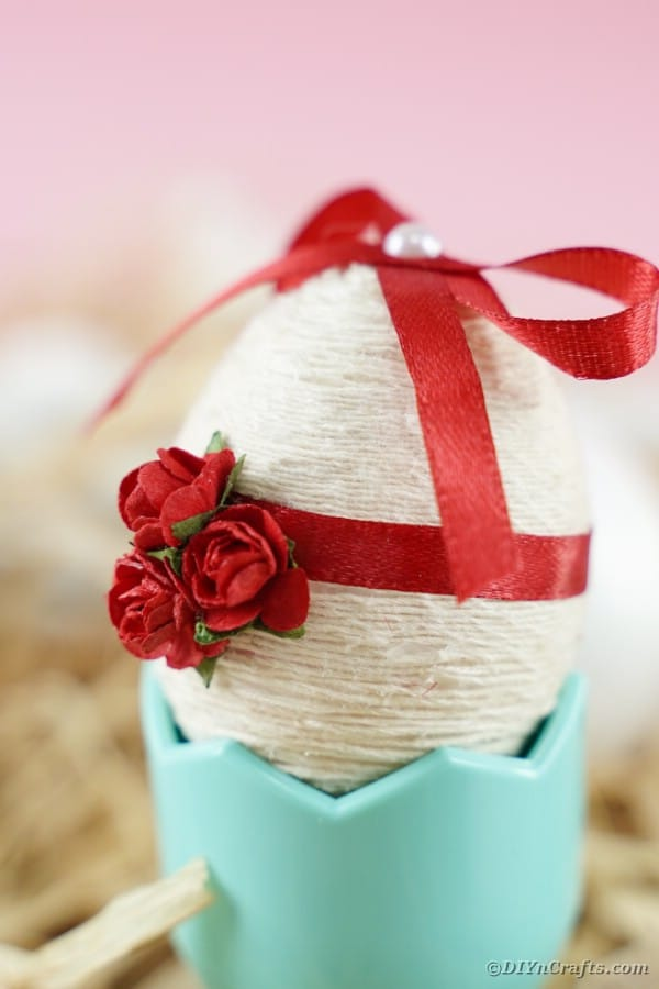 Side view of a yarn and ribbon covered Easter egg
