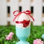 Yarn egg in blue egg cup in front of fence
