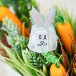 Egg carton Easter bunny on greenery with carrots