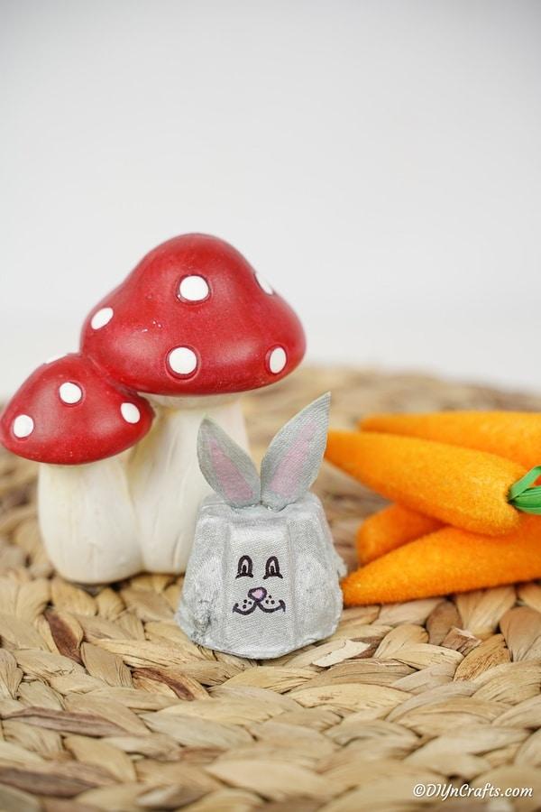 Egg carton bunny on woven mat by mushroom decor