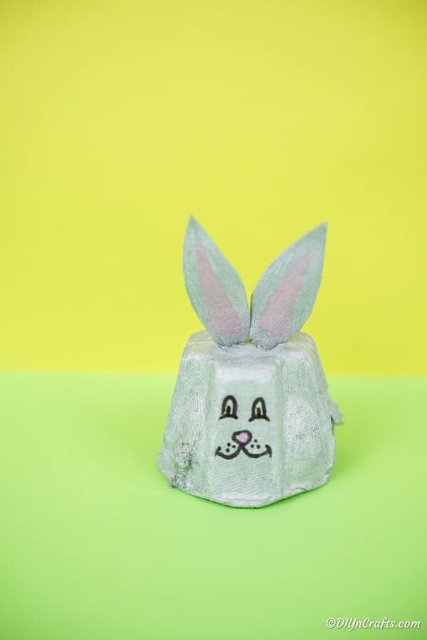 Egg carton Easter bunny on green surface