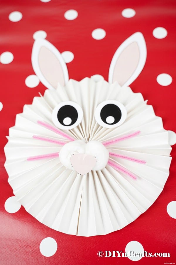 Paper bunny on red and white polka dot background