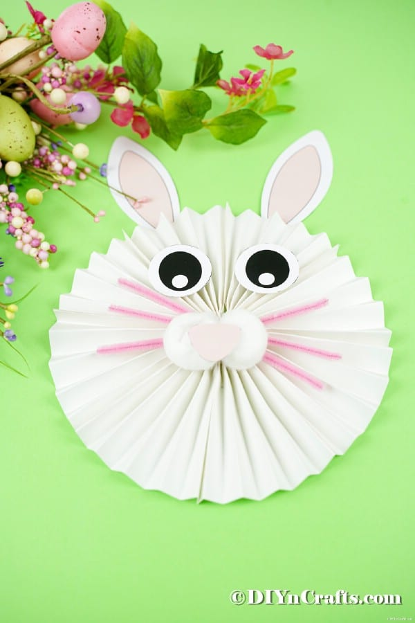 Easter bunny craft on green table by flowers