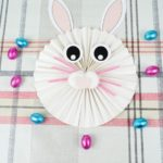 Paper bunny on striped tablecloth