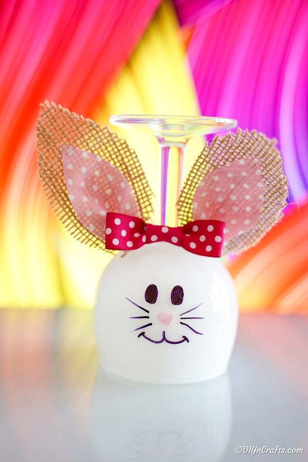 Easter bunny wine glass in front of colorful background