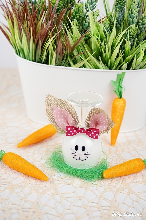 Wine glass bunny in front of potted plant