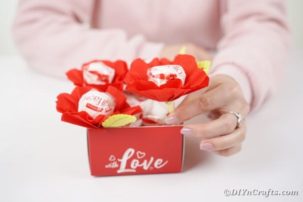 Woman putting paper flower candy in box