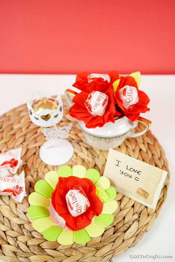 Red paper flower candy wrappers on woven mat