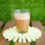 Green clothespin coaster on table in front of grass