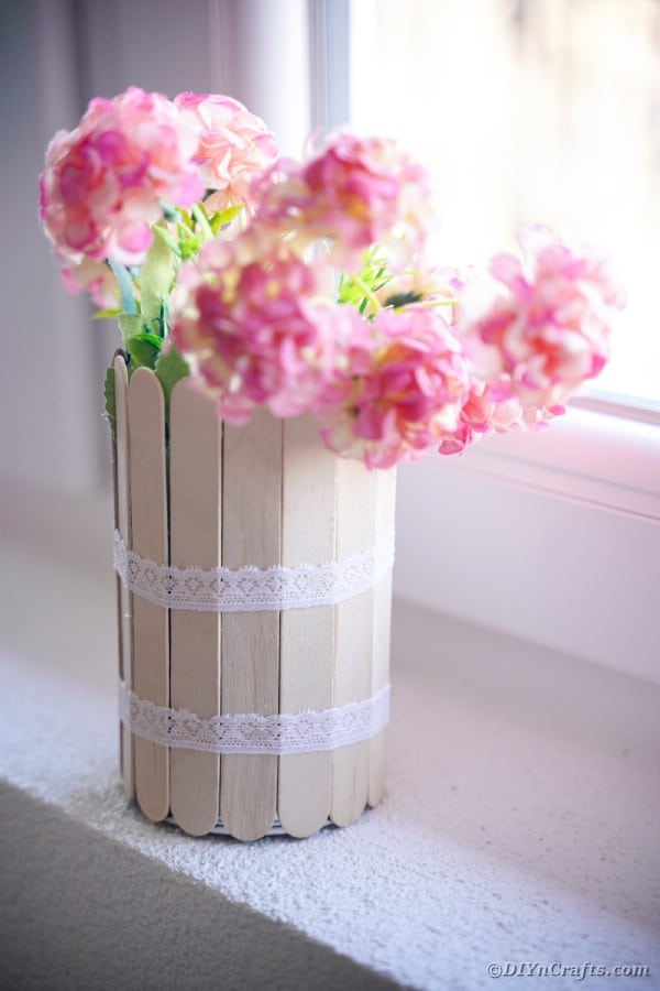 Craft stick can with pink flowers on windowsill