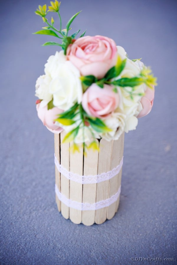 Craft stick vase with white and pink flowers on sidewalk