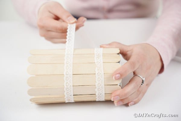 Gluing lace around craft stick tin can