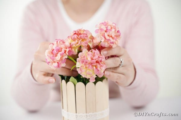 Woman arranging flowers in craft stick can