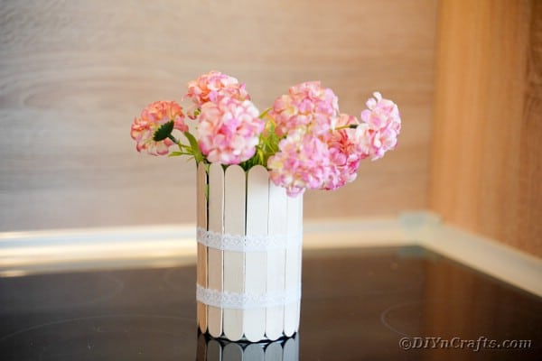 Craft stick can with pink flowers on wood table