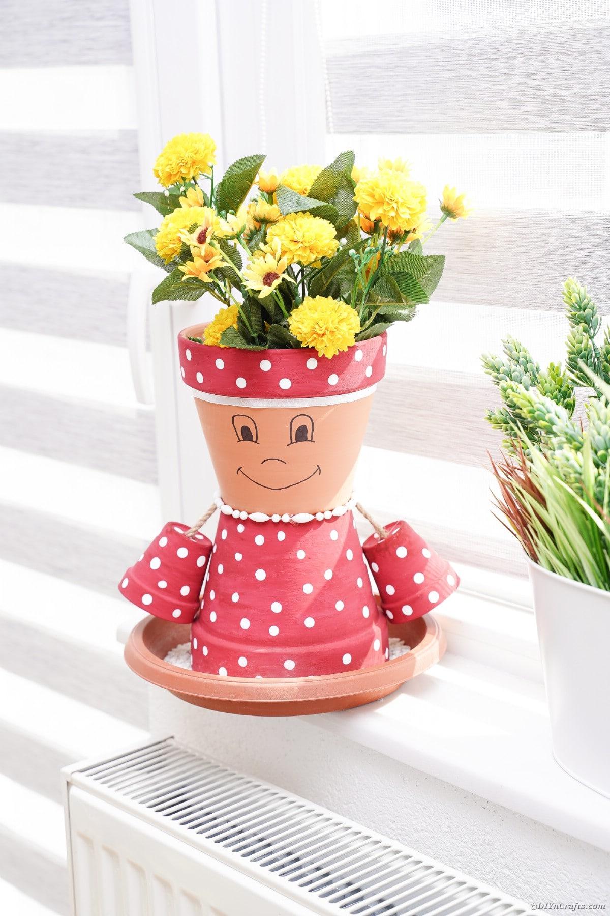 Pink polka dot flower pot in windowsill