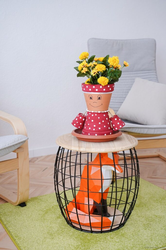 Flower pot person on wooden stool
