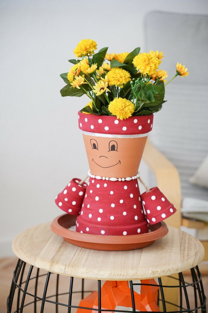 Pink and white polka dot clay pot person on stool