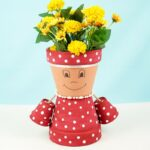 Flower pot girl on table with blue background