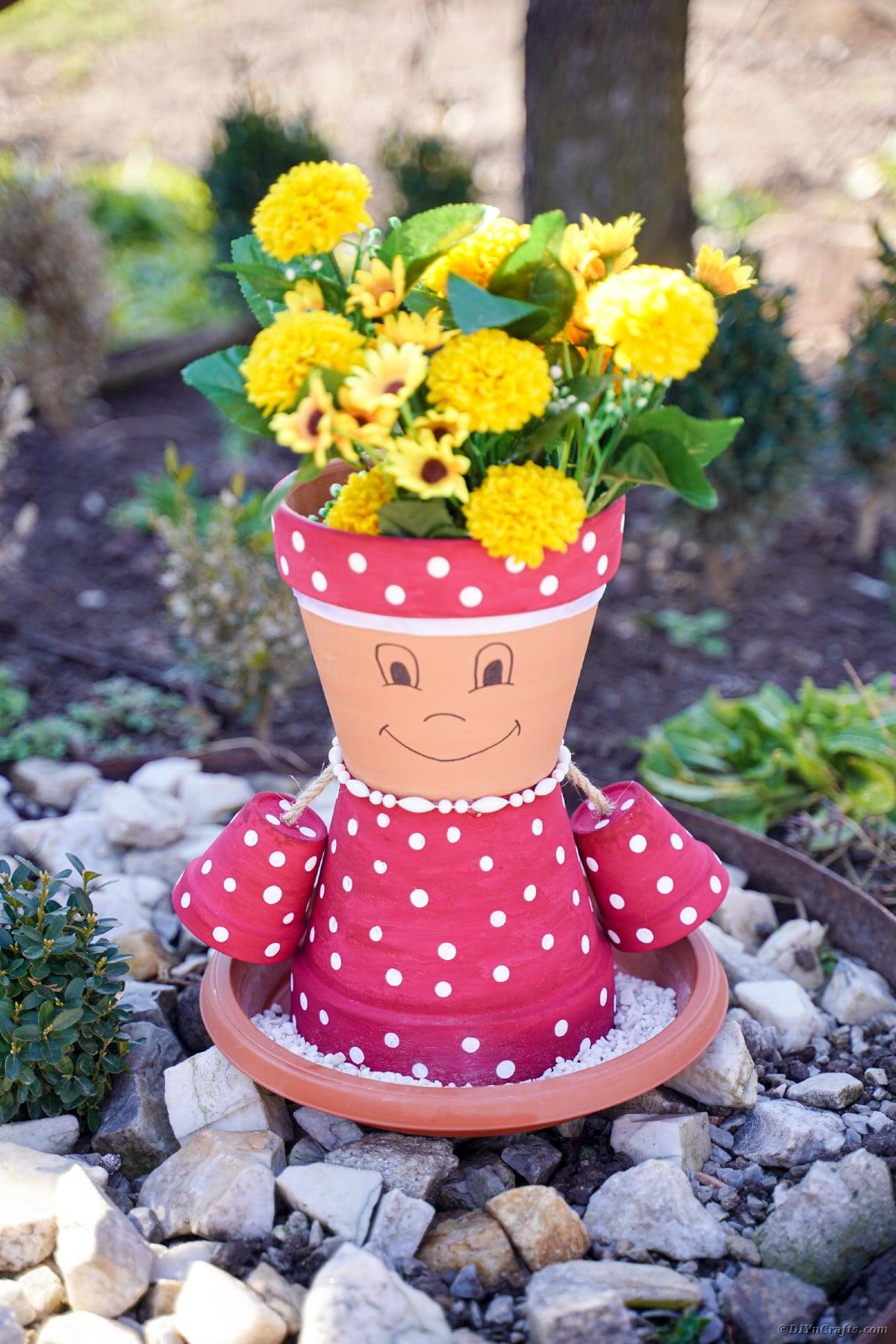 Flower pot person on rocks outside