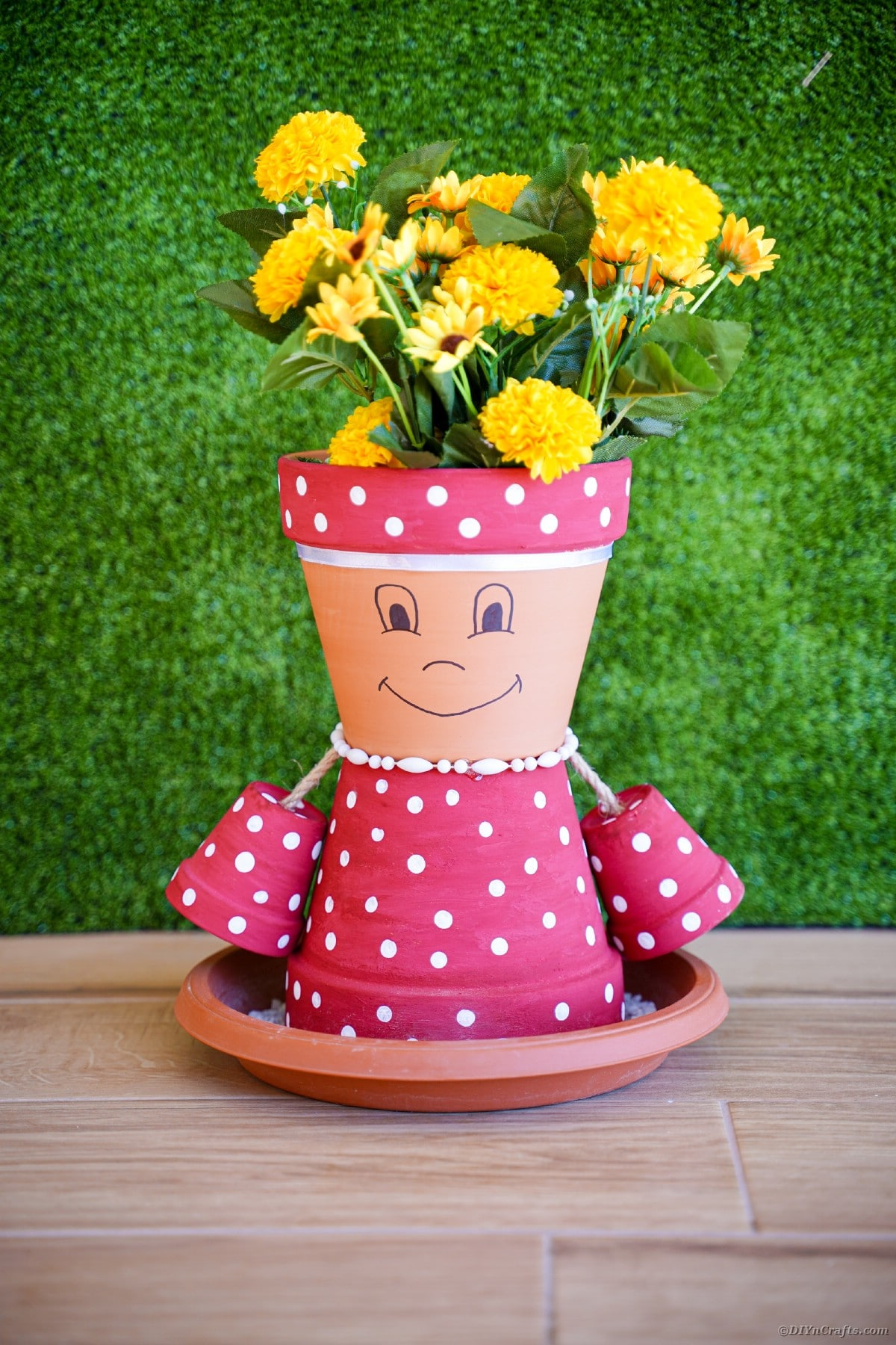 Flower pot girl on table in front of grass
