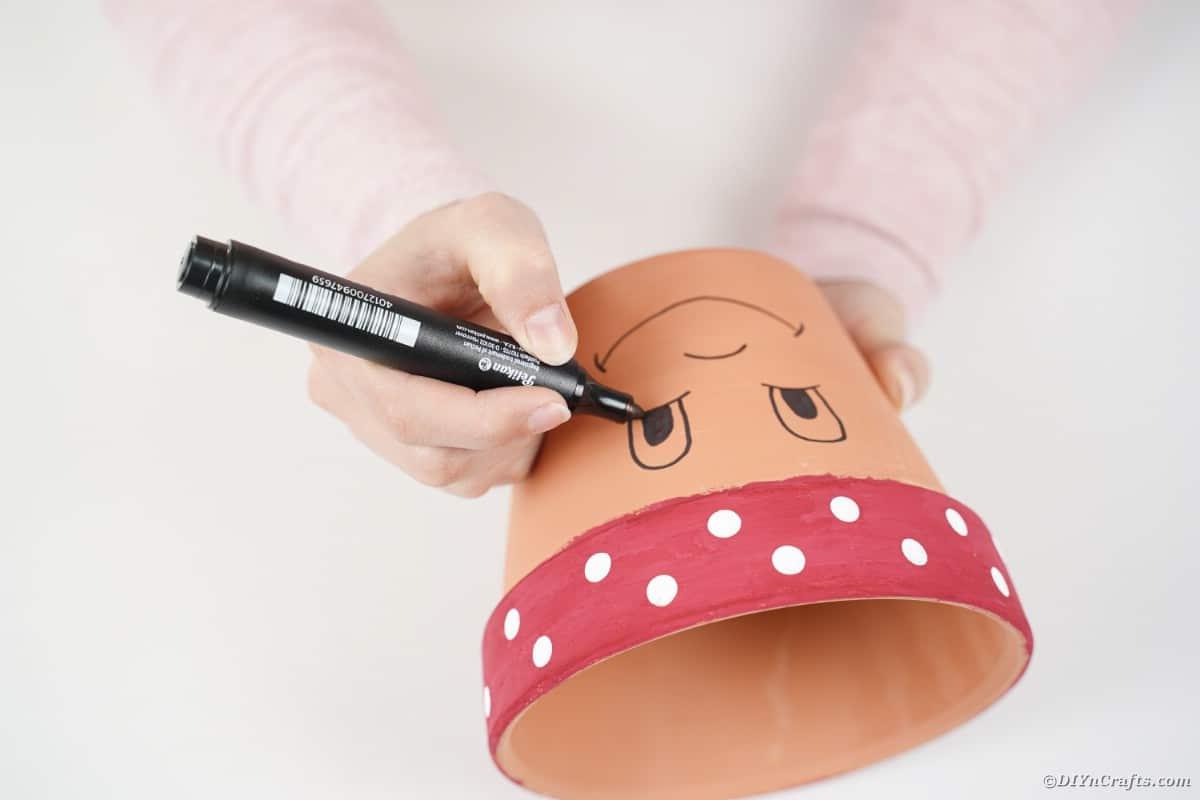 Drawing a face onto a flower pot