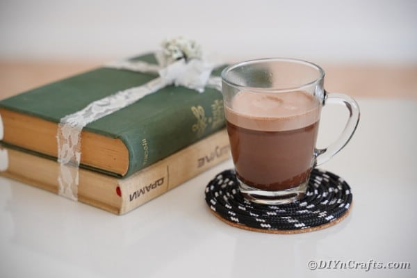 Glass of coffee on black coaster on side table by books
