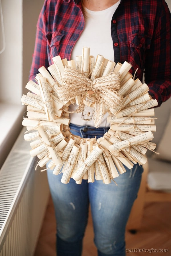 Woman holding an old book page wreath