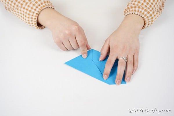 Hands folding blue paper