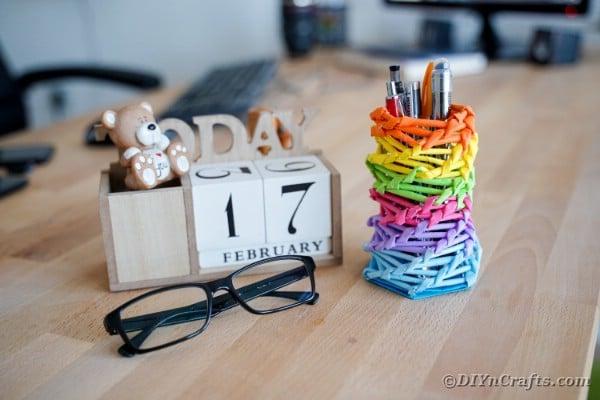 Rainbow pencil holder on desk by block calendar
